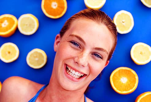 Laughing teen girl surrounded by orange halves