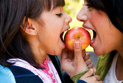 Mother and daughter sharing apple