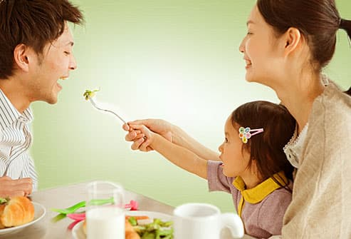 Parents sharing salad with little girl
