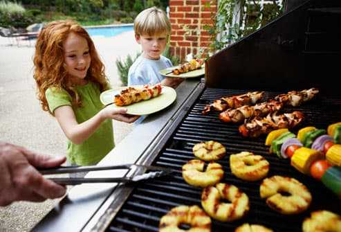 Family grilling fruits and veggies