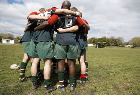 Rugby players standing in circle on sports field