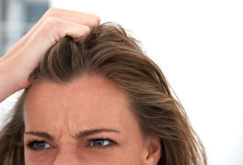 Woman pulling her own hair in anger