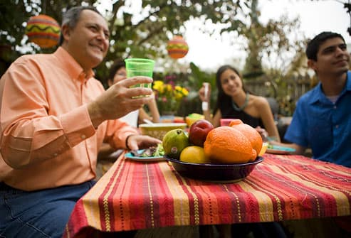 smiling family having a meal at a picnic table