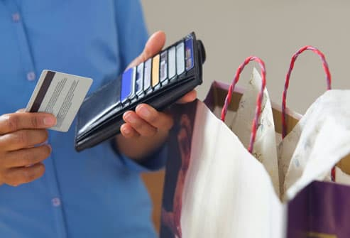 Close-up of hands pulling credit card from wallet
