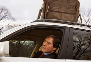 Business man with briefcase on car roof