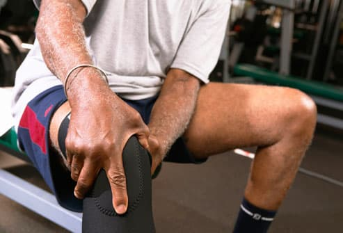 Man Holding Knee in Brace