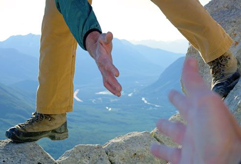 Hiker Extending Hand to Another Man