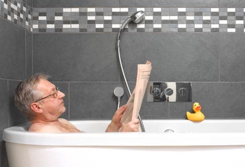 older man reading in bathtub