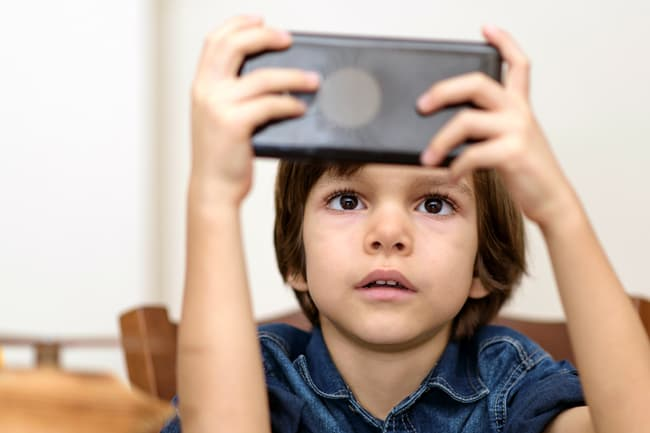 photo of child playing with handheld video game