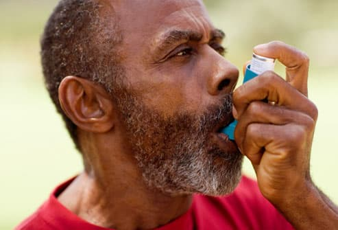 Mature man using COPD inhaler