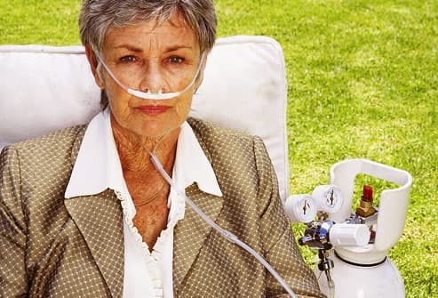 Mature woman using portable oxygen tank