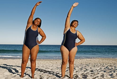Two Women Stretching on Beach