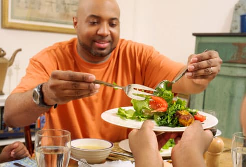 Father Serving Salad onto a Plate