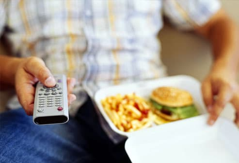 Man using remote control holding takeout food