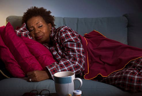woman with the flu laying on couch