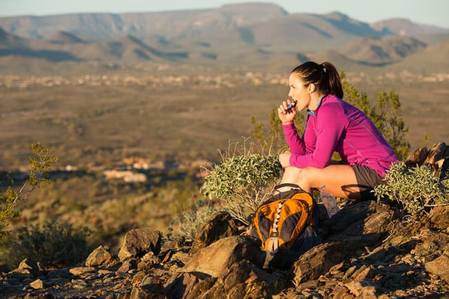 photo of person eating snack on trail
