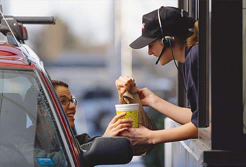 fast-food employee gives a customer her order