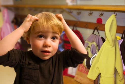 boy scratching head in coatroom