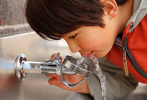 boy drinking from fountain