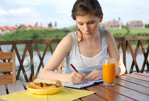 woman eating and taking notes
