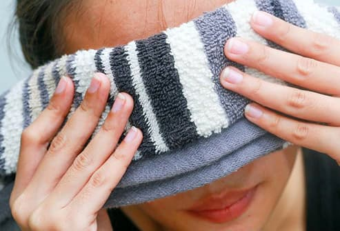 woman with washcloth over eyes
