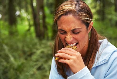Dissatisfied woman biting into a granola bar