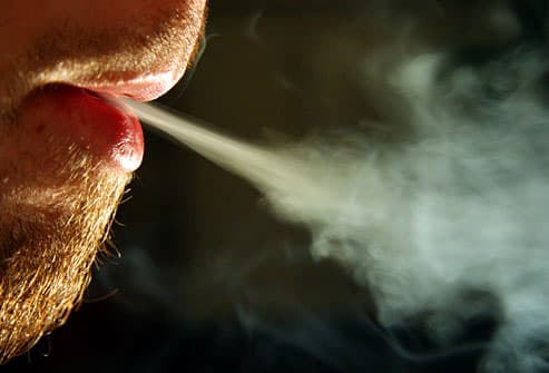 Closeup of a man exhaling cigarette smoke