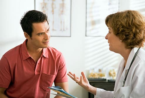 Man talking to doctor in exam room