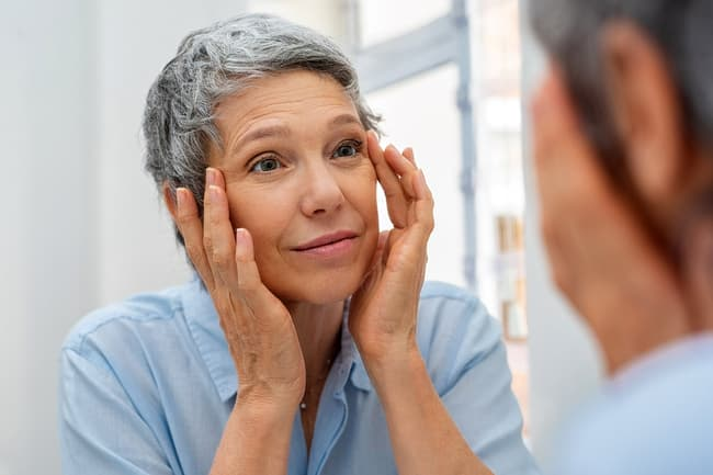 photo of mature woman looking in mirror