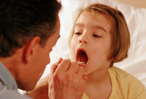 doctor using a tongue suppressor to check tonsils