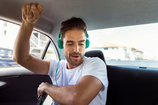photo of man in car listening to music