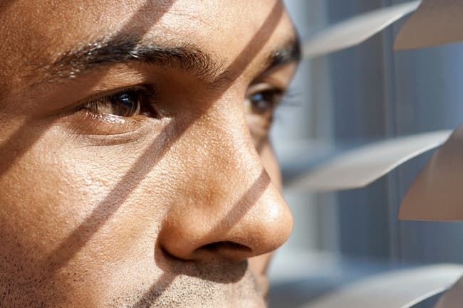 photo of man looking through window blinds
