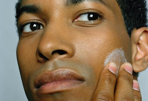 man applying moisturizers