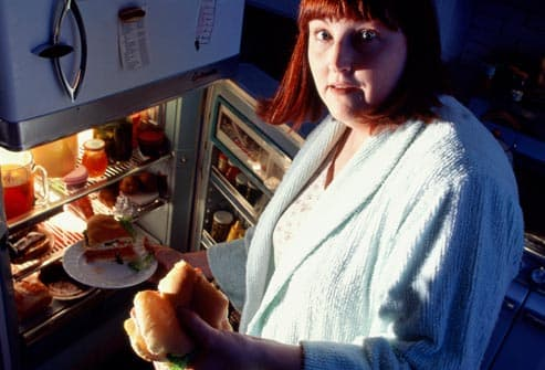 woman raiding refrigerator at night