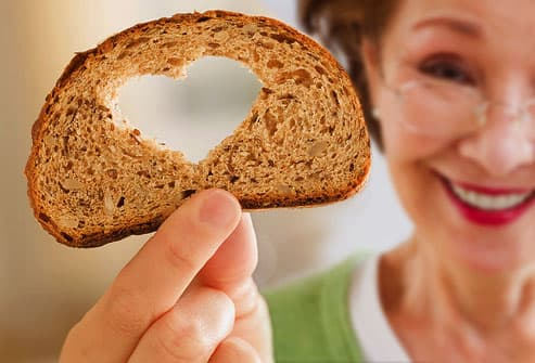 Mature woman holding whole grain bread