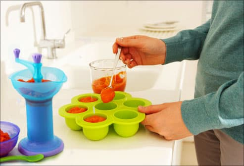 Woman preparing homemade baby food from carrots