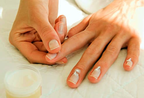 woman applying lotion to her nails
