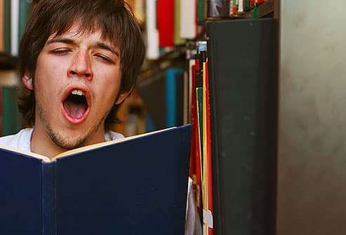 boy yawning in library