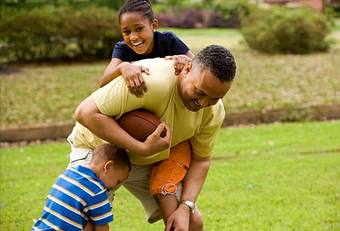 Father playing football with kids