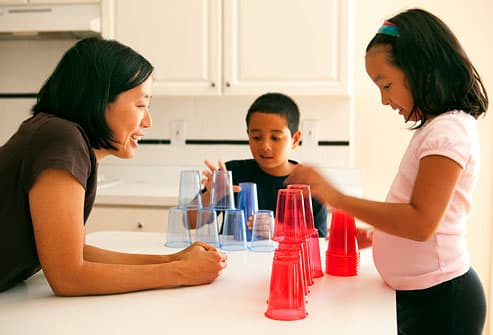 Family playing cup stacking game