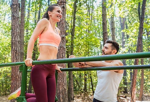 woman using parallel bars outside