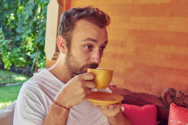 photo of man drinking coffee on porch