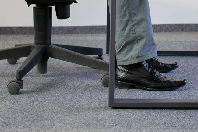 photo of feet on floor under desk