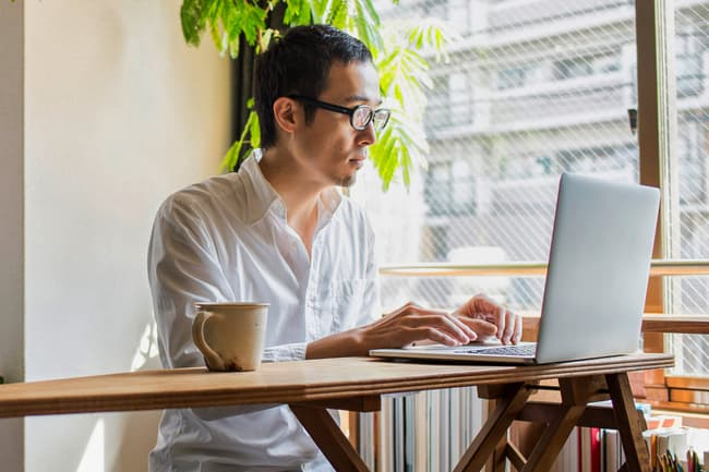 photo of man using laptop by window