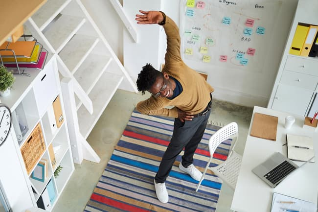 photo of man stretching in office