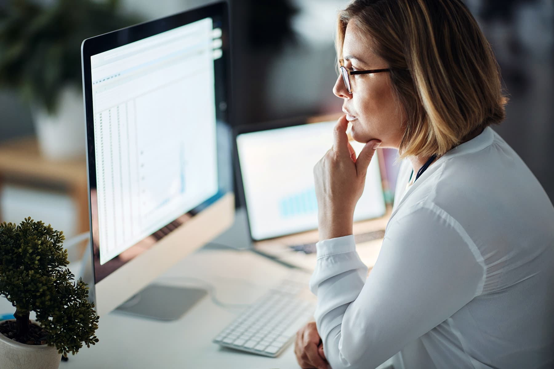 photo of woman using two computer screens