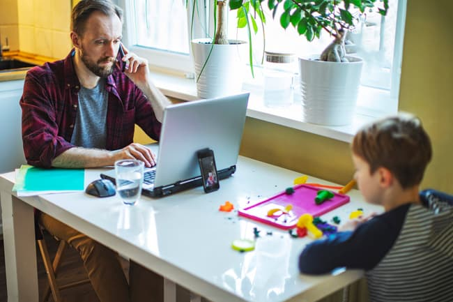 photo of man working next to son at home