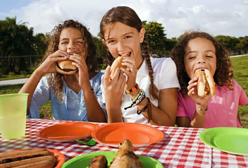 Girls eating beef at picnic