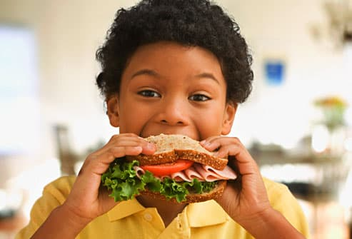 Boy eating ham sandwich with lettuce on whole whea