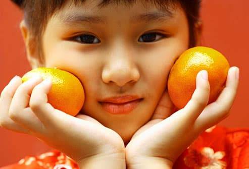 Asian girl holding two oranges to her cheeks